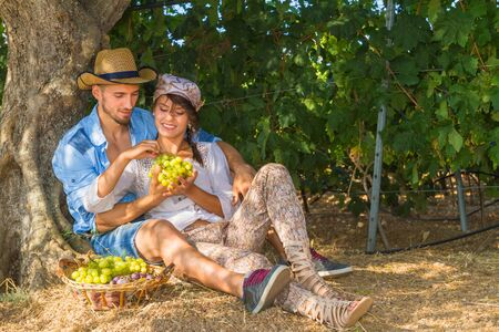 Happy young farmers enjoy a work break sitting at the shade of a tree at the vineyard, eating grapes, kissing, feeding, and teasing one another. photo