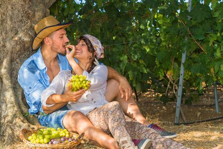 teasing: Happy young farmers enjoy a work break sitting at the shade of a tree at the vineyard, eating grapes, kissing, feeding, and teasing one another. Stock Photo