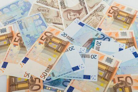 savings and loan crisis: Old Greek 1000 drachmas banknotes and variety of euro bills.
