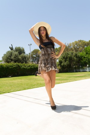 mini dress: Playful young beautiful and expressive dark haired girl wearing a mini dress, a white straw hat, and high heels enjoys a hot summer day practicing and improvising theatrical posing and expressions.