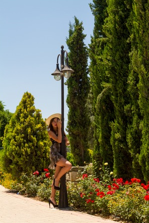 sexual activities: Playful young beautiful and expressive dark haired girl wearing a mini dress, a white straw hat, and high heels enjoys a hot summer day practicing and improvising theatrical posing and expressions.