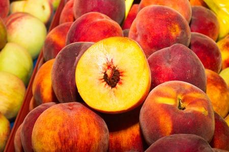super fruit: High energy food, health booster super fruit, juicy peaches on an open air fruit market bazaar.
