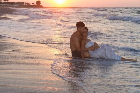 getting late: Just married young couple at the beach , in a late summer hazy day at dusk, wearing  a wedding dress and shorts, enjoying walking barefoot, getting wet, teasing and kissing one another.