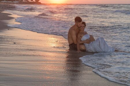 wet dress: Just married young couple at the beach , in a late summer hazy day at dusk, wearing  a wedding dress and shorts, enjoying walking barefoot, getting wet, teasing and kissing one another.