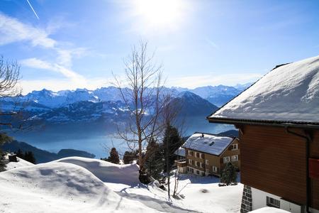 雪をかぶったシャレーと山霧 Vierwaldstattersee、リギ、ルツェルン湖、スイスの地平線を見渡すパノラマ ビュー 写真素材