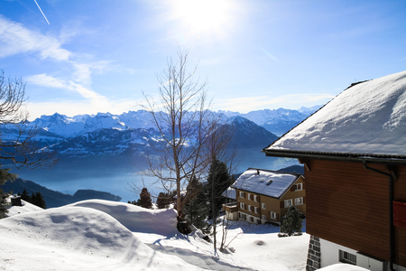 chalets: Panoramic skyline view of snow-capped chalets and mountains over foggy Vierwaldstattersee, Rigi, Lake Lucerne, Switzerland Stock Photo
