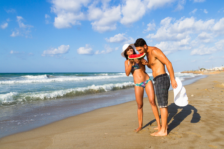 bikini couple: Happy attractive young couple in bikini and shorts enjoying a summer dusk at the beach, having fun walking barefoot, sharing a slice of watermelon,  and teasing one another. Stock Photo