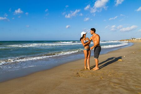 girl in a hat: Happy attractive young couple in bikini and shorts enjoying summer dusk at the beach, practicing fitness exercises, having fun walking barefoot, kissing and teasing one another. Stock Photo