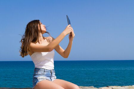 nude body: Gorgeous young beautiful long haired teenage brunette in jean shorts enjoys the sun seated on a stone wall on a spring morning by the ocean, and poses for selfies using a tablet.