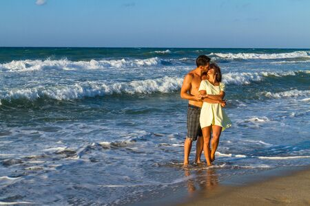 beachwear: Happy attractive young couple in beachwear, enjoying a summer dusk at the beach, having fun walking barefoot, getting wet, kissing and teasing one another. Stock Photo