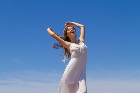 Young long haired brunette girl, pure angelic innocence in white flimsy dress, enjoying the sun on a fresh spring day.