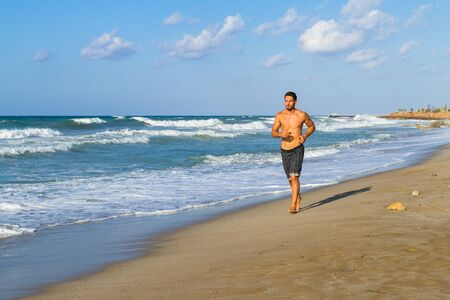 twenties: Young man in his twenties jogging along the shoreline on a sandy beach, late afternoon in the summer.