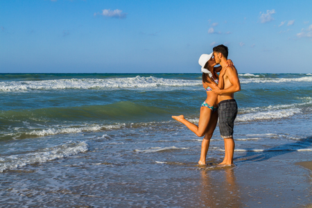 ragazza innamorata: Happy attractive young couple in bikini and shorts enjoying summer dusk at the beach, practicing fitness exercises, having fun walking barefoot, kissing and teasing one another. Archivio Fotografico
