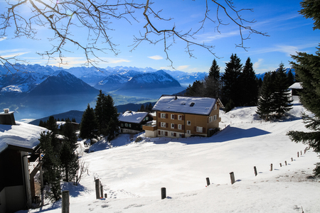 chalets: Panoramic skyline view of snow-capped chalets and mountains over foggy Vierwaldstattersee, snow covered Rigi, Lake Lucerne, Switzerland