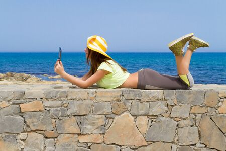 beachwear: Beautiful young long haired brunette teenager in beachwear and hat, enjoying the summer sun by the ocean, while posing for selfies using a tablet. Stock Photo