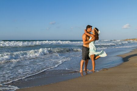 wet dress: Loving young couple at the beach in a late summer hazy day at dusk, wearing a turquoise dress and shorts, enjoying  going barefoot in the ocean water, getting wet, teasing and kissing one another.