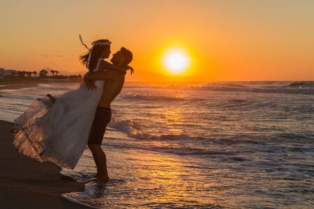 wet dress: Backlit partially silhouetted newly wed young couple at the beach, enjoying the beautiful hazy sunset, wearing a wedding dress and shorts, barefoot, getting wet, teasing and kissing one another.