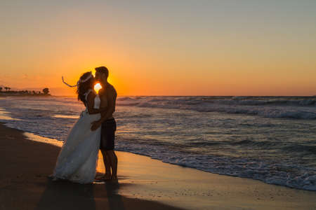 young couple kissing: Backlit partially silhouetted newly wed young couple at the beach, enjoying the beautiful hazy sunset, wearing a wedding dress and shorts, barefoot, getting wet, teasing and kissing one another.