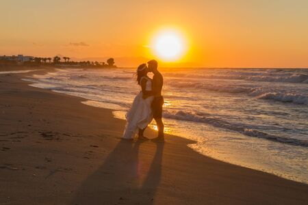 teasing: Backlit partially silhouetted newly wed young couple at the beach, enjoying the beautiful hazy sunset, wearing a wedding dress and shorts, barefoot, getting wet, teasing and kissing one another.