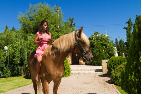 woman and horse: Beautiful young barefoot modern brunette amazon with red dress, riding a slender brown-blond purebred horse without a saddle.