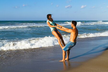 beach girl: Happy attractive young couple in bikini and shorts enjoying summer dusk at the beach, practicing fitness exercises, having fun walking barefoot, kissing and teasing one another. Stock Photo