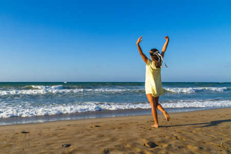 young girl barefoot: Barefoot young woman enjoys time on a sandy beach in summer, at dusk. Stock Photo