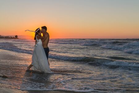 wet dress: Just married young couple at the beach, enjoying the hazy dusk, wearing a wedding dress and shorts, walking barefoot, getting wet, teasing and kissing one another.