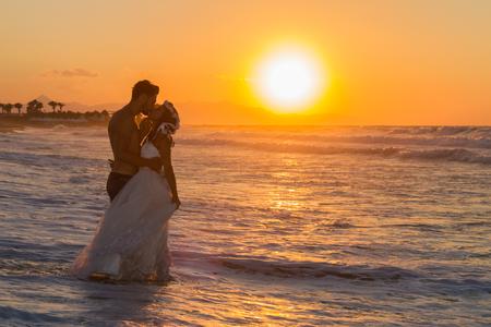 casados: Apenas casado joven pareja en la playa, disfrutando del atardecer brumoso, que llevaba un vestido de novia y pantalones cortos, caminar descalzo, mojarse, las burlas y besándose el uno al otro. Foto de archivo
