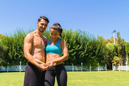 healthy sport: Delighted young athletic couple in sportswear measuring their waistline after a workout at the park. Healthy lifestyle and fitness concept.