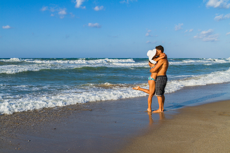 bikini couple: Happy attractive young couple in bikini and shorts enjoying summer dusk at the beach, practicing fitness exercises, having fun walking barefoot, kissing and teasing one another. Stock Photo