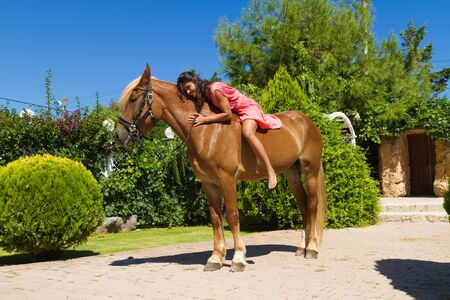 Beautiful young barefoot modern brunette amazon with red dress, on a slender brown-blond purebred horse without a saddle. Selective focus. Sports and lifestyle concept.