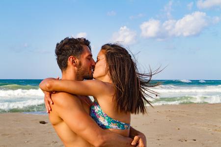 besos hombres: Pareja joven abrazando y besando en la playa al final del verano al atardecer.
