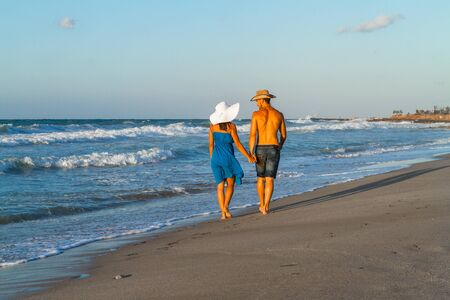 woman beach dress: Happy young couple in jean shorts, a blue dress, wearing hats, walking along a wet sandy beach, at dusk.