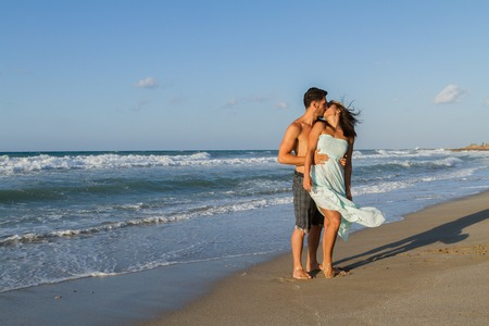 activities: Young couple at the beach on a  hazy summer day at dusk, wearing a turquoise dress and shorts, enjoying  walking barefoot in the ocean water, getting wet, teasing and kissing one another.