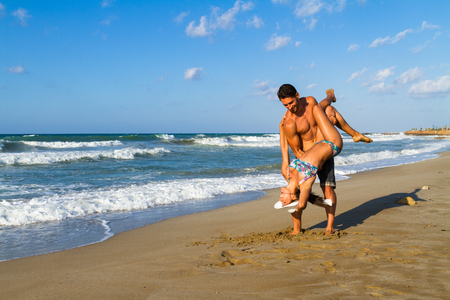 summer vacation bikini: Happy attractive young couple in bikini and shorts enjoying summer dusk at the beach, practicing fitness exercises, having fun walking barefoot, kissing and teasing one another. Stock Photo