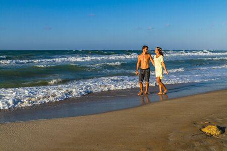 parejas romanticas: feliz pareja joven y atractiva en ropa de playa, disfrutando de un atardecer de verano en la playa, que se divierten caminar descalzo, mojarse, los besos y las burlas entre sí.