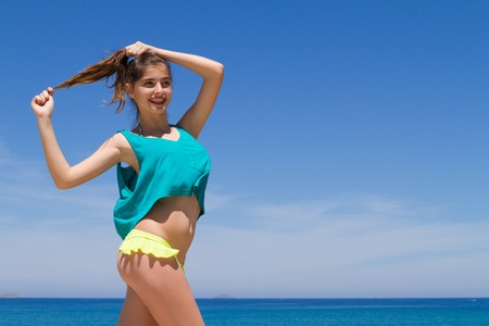 Long haired cheerful teenage brunette in beachwear, enjoys summer by the ocean. Stock Photo