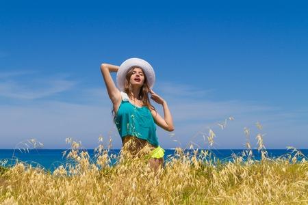 beachwear: Long haired cheerful teenage brunette in beachwear, enjoys summer by the ocean. Stock Photo