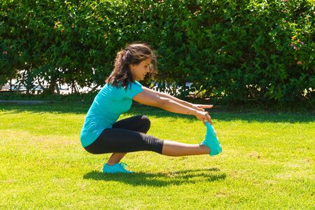 strong girl: Beautiful athletic young woman in sportswear working out outdoors in the park on a summer day, stretching hamstrings. Healthy lifestyle, and fitness concept.