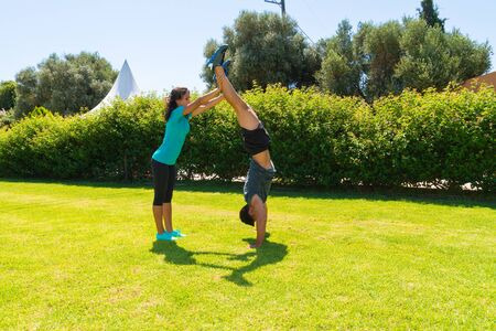 mascular: Young slim athletic man in sportswear doing handstands on the grass, assisted by female trainer. Healthy lifestyle, fitness concept. Stock Photo