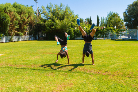 mascular: Young slim athletic couple in sportswear doing handstands on the grass, walking upside-down using their hands as feet, in the summer. Healthy lifestyle and fitness concept.