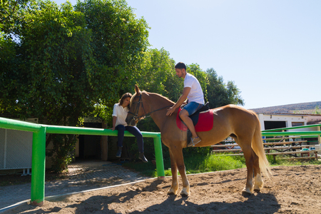 horse sleigh: Young couple practices horseback riding lessons with a brown-blond purebred mare in the riding club arena. Stock Photo