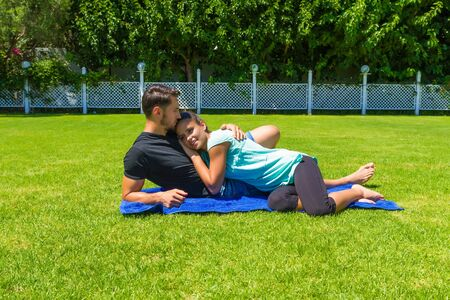 teasing: Happy young couple in casual wear, barefoot, relaxing enjoying the sun lying on the grass in summer, having fun chatting, teasing and kissing one another. Stock Photo