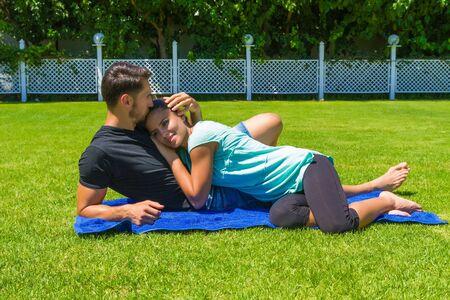 femme romantique: Bonne jeune couple dans des v�tements d�contract�s, pieds nus, se d�tendre en profitant du soleil couch� sur l'herbe en �t�, amusant bavarder, taquiner et embrasser les uns les autres.