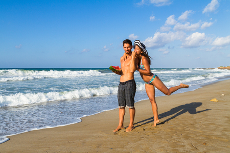 girl in shorts: Playfull attractive young couple in bikini and shorts enjoying a summer dusk at the beach, having fun walking barefoot, sharing a slice of watermelon,  and teasing one another. Stock Photo