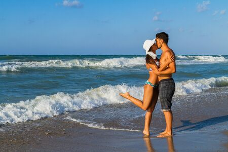 fresh girl: Playfull attractive young couple in bikini, white hata nd shorts enjoying a summer dusk at the beach, having fun walking barefoot, teasing and kissing one another. Stock Photo