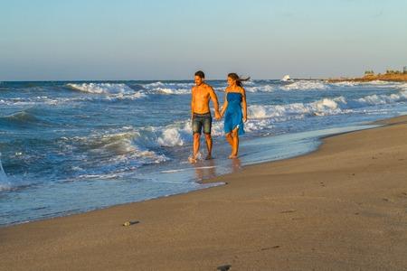 femme romantique: Bonne jeune couple dans un short en jean, une robe bleue, marchant le long d'une plage de sable humide, au cr�puscule.