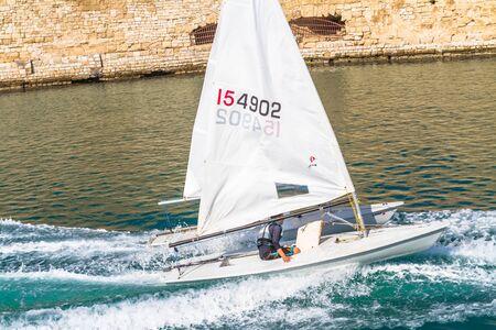 towed: Heraklion Crete Greece Nov 3,  2013. Worried young trainee yachtsman on a speeding beginners laser sailing boat being towed for a sailing training exercise. Editorial