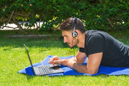 people relaxing: Young man using a laptop and headphones,  lying on grass in the city park. Lifestyle, education, and digital communication technology concept.