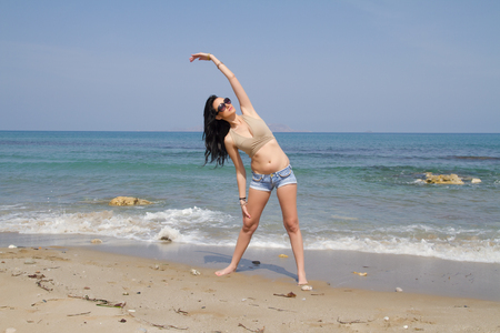 beachwear: Beautiful long haired woman in beachwear and sunglasses does fitness workout at the beach in the summer.